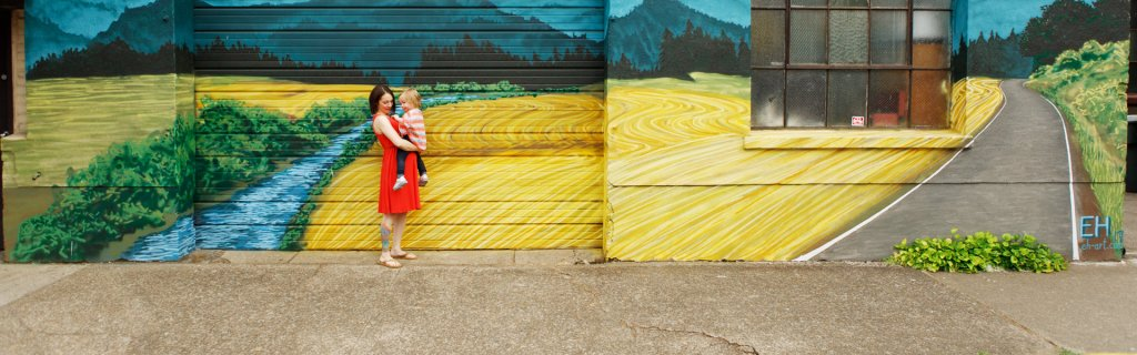 a woman and small child stand in front of a building where a mural has been painted