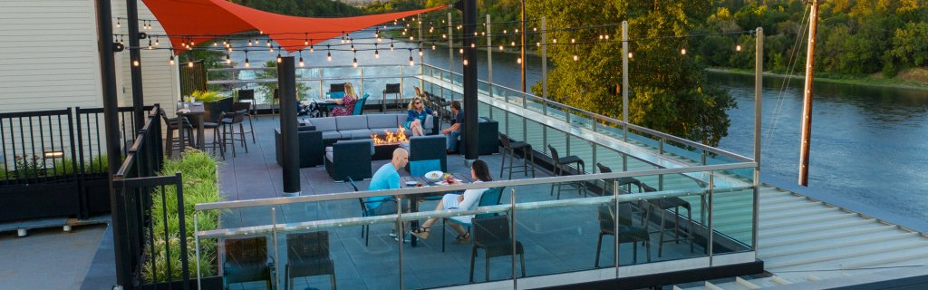 A light strung patio with people drinking and eating that over looks the river