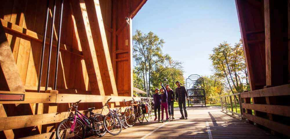 Friends with bicycles gather and are staring up into a covered bridge