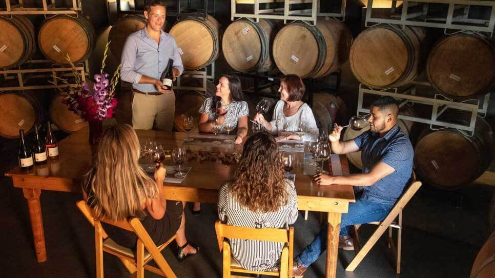 a group of five gather are seated at a table for a wine tasting in a room full of barrels.