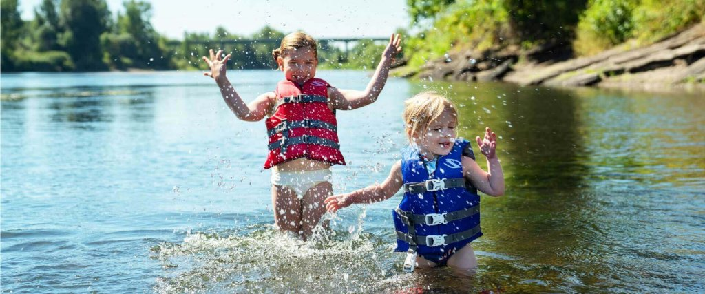 two young girls splash in the water wearing life jackets