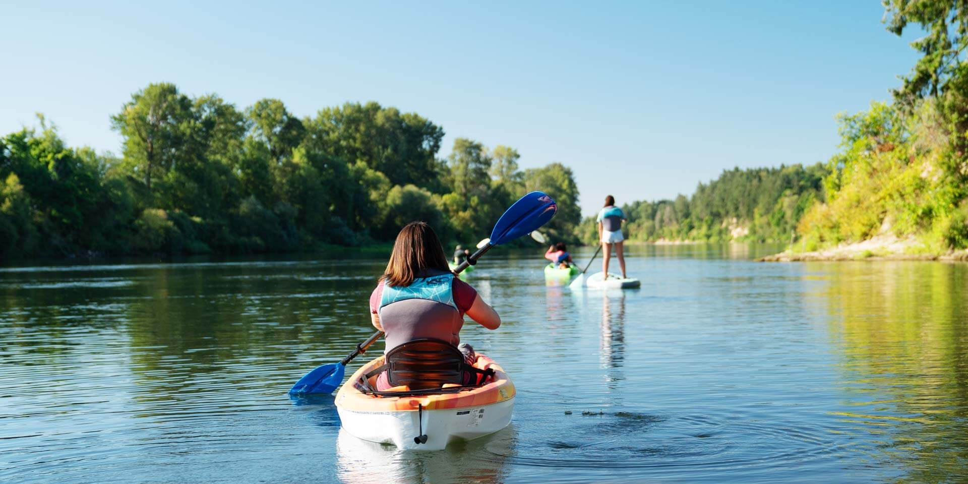 A girl is kayaking and her friends are up ahead paddle boarding on a still river