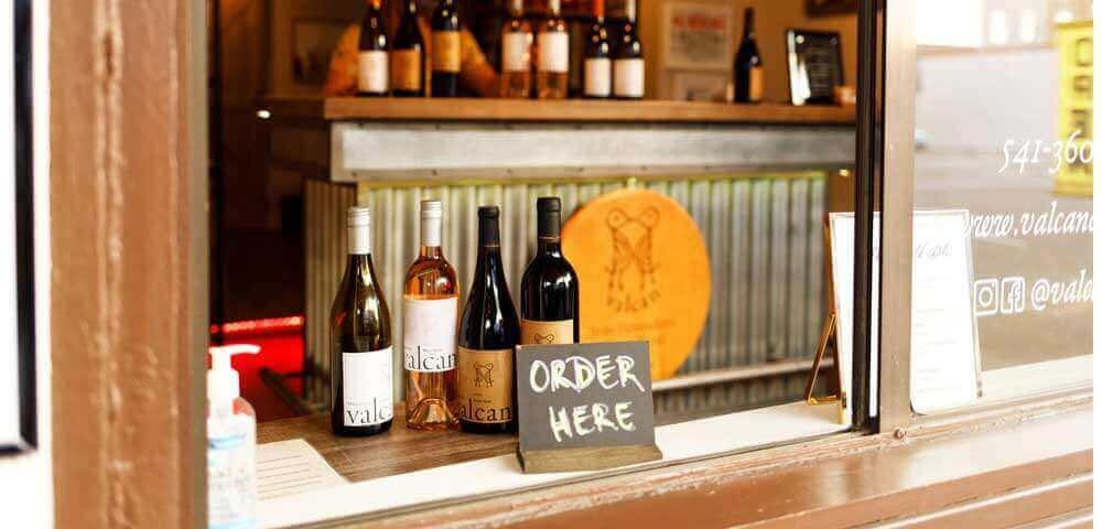 """a chalk drawn sign reads, """"Order Here,"""" in front of a counter full of wine"""