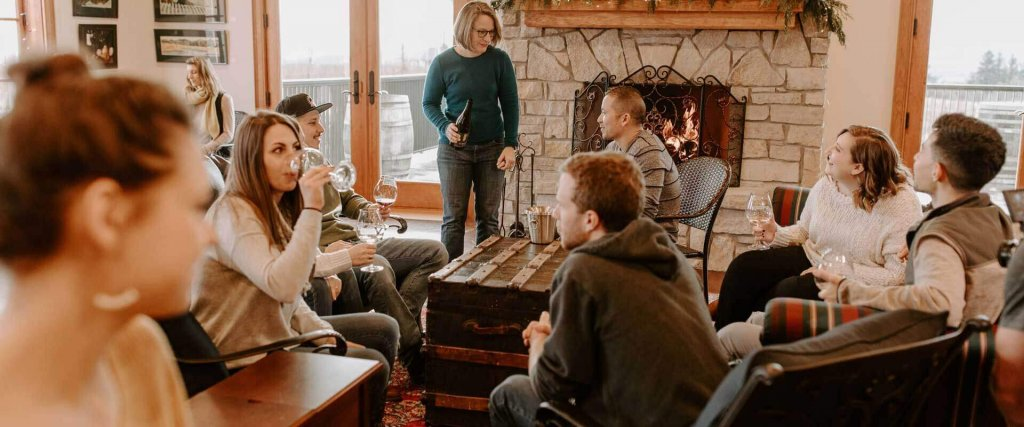 a group gathers around in a living area space with a fireplace