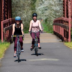 female bikers cross over a red wrought iron birdge