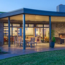 A modern winery building has an open patio overlooking the vineyard property.