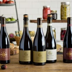 Seven bottles of Soter wine sit on a wooden table in the Soter Marketplace.