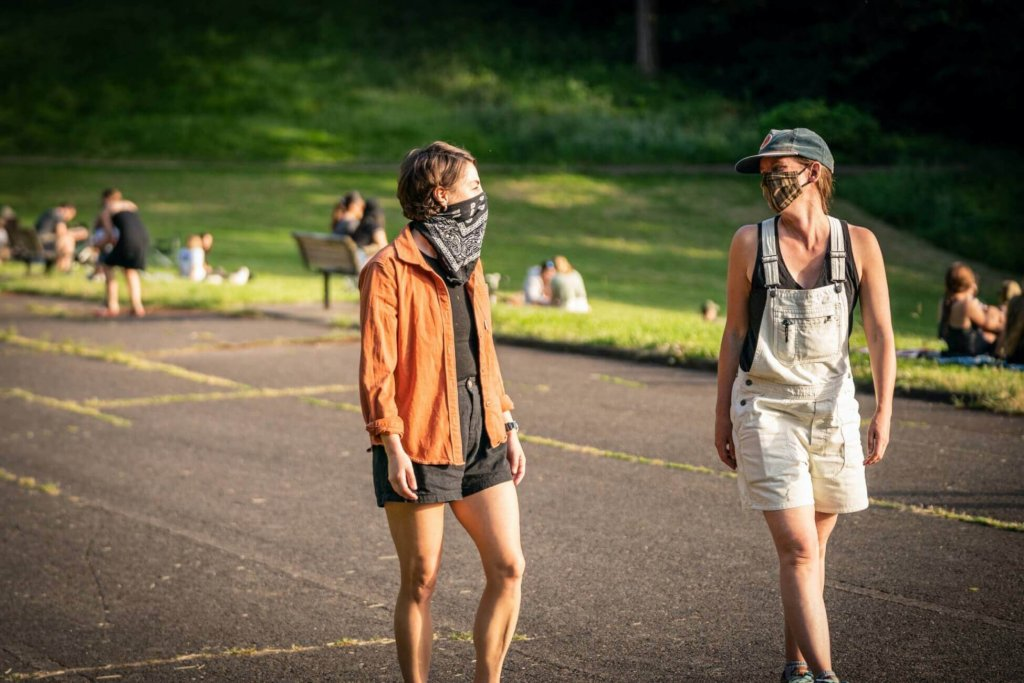 Two women wearing masks walk down a path at a park, visitors are seated in the grass behind them.