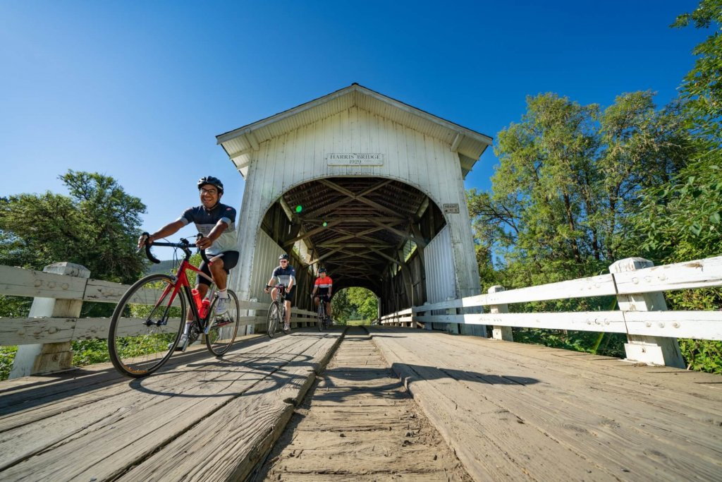 Three cyclists ride on a path of wooden planks as they exit a white covered bridge.