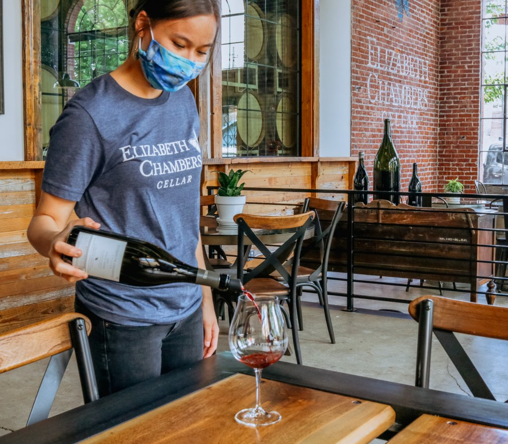 Woman wearing aa mask pouring a bottle of wine