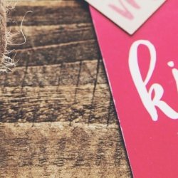 """A red and white """"kiss me"""" gift tag sits on a wooden table."""
