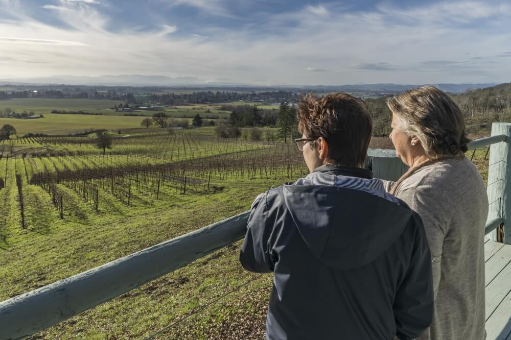 Two women look over a vineyard on a sunny day