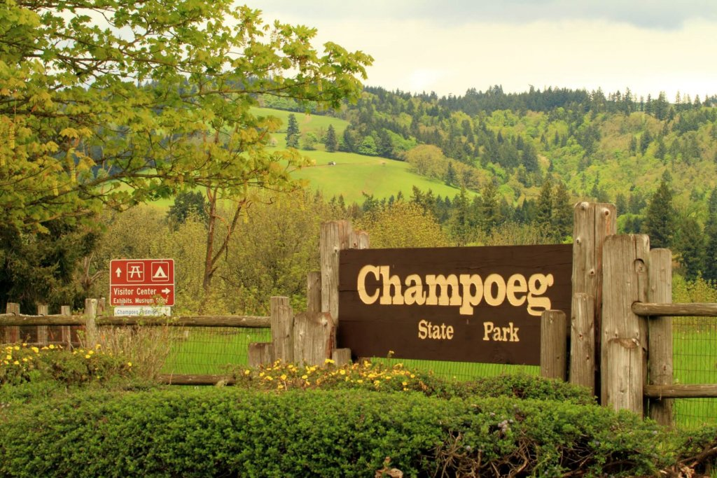The sign for Champoeg State Park sits amid rolling green hills with a mix of green trees.