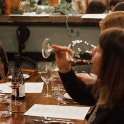 group of people enjoying glasses of wine during dinner at a restaurant