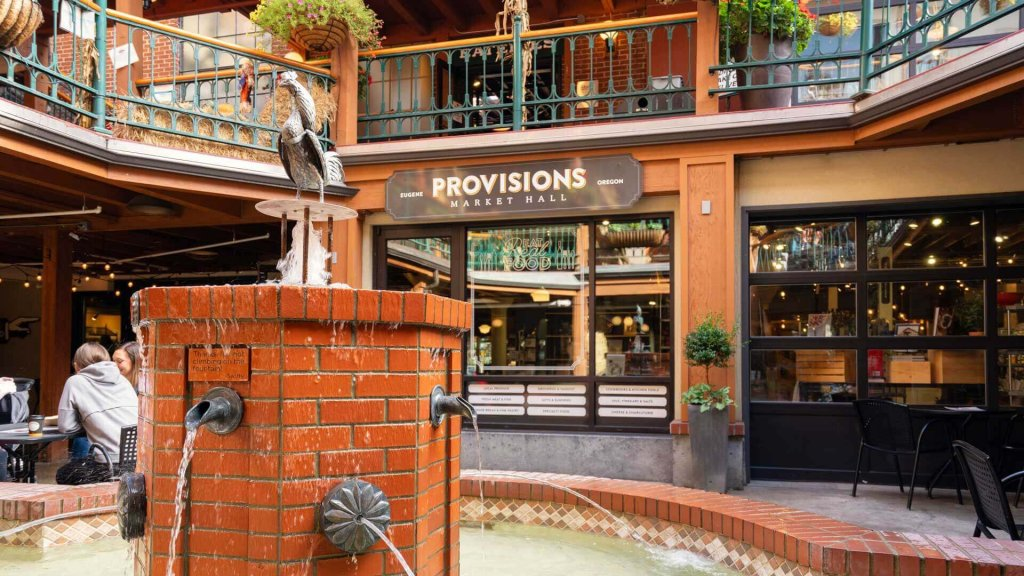 Outside of Provisions Market Hall where two guests sit at a table drinking coffee with a water fountain in the foreground