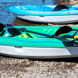 Two kayaks and a cooler on the river's edge