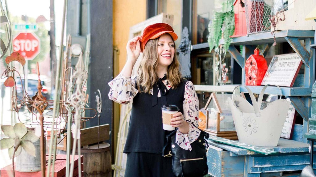 A woman browses an eclectic shop and tries on a red hat with a coffee in her hand