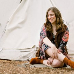 A woman sits and smiles in front of a tipi