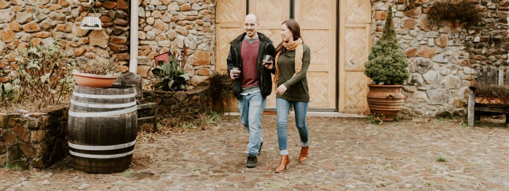 Couple walks outside of a wine cellar with wine glasses in hand