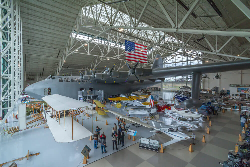 Visitors to the Evergreen Aviation Museum tour a large, airy warehouse filled with a variety of aircraft in McMinnville, Oregon..