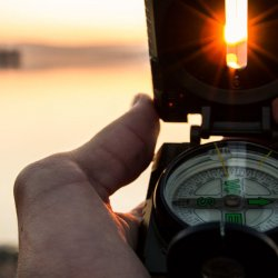 man holding compass overlooking a lake with the sun on the horizon