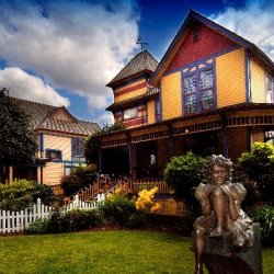 A bronze statue of a child sits in the lawn of the Gilbert House Children's Museum, housed in a brightly colored Victorian style home.