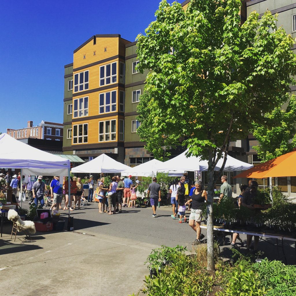 a small crowd can be seen at a Farmers Market in the Willamette Valley. There is a yellow and olive green building in the background