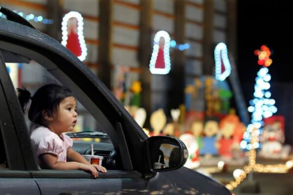 A little girl in a car looks at holiday lights out of the window