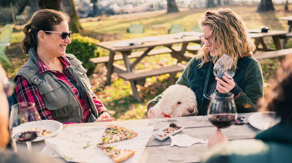 Women sitting at a picnic table eating pizza