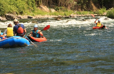 Two men in red kayaks and a couple in a blue river raft ride the mini rapids