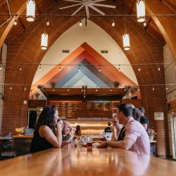 A small group of friends sits at a long table in a brewery with church-like arched ceilings and stained glass windows.