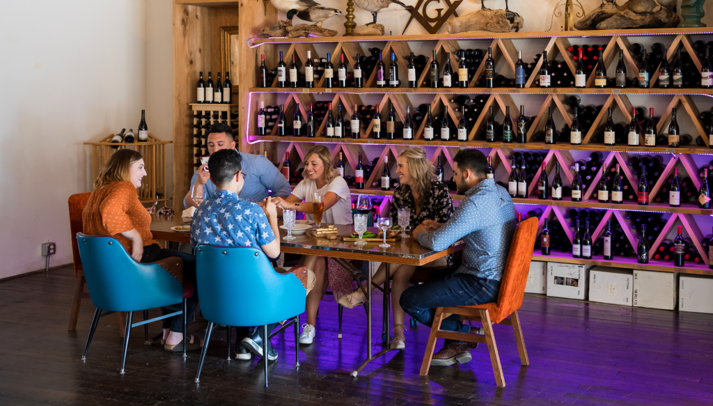 Group of people eating in a local restaurant with wine on the wall behind them