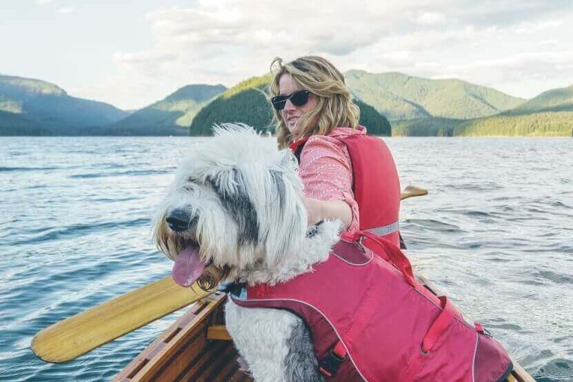 A woman takes her shaggy dog out on a wooden canoe for a paddle on Detroit Lake.