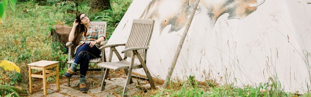 woman sits in a chair outside of a tipi at Tipi Village