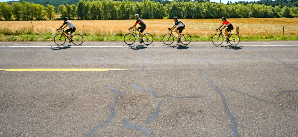 four cyclers on a road